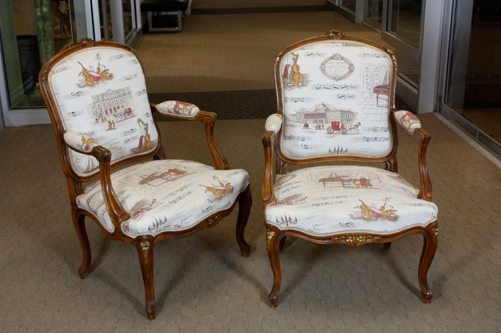 Pair of nicely-carved French, Louis XV style fruitwood fauteuils with gilded flowers on the crest rail, seat rail and knees. Recently upholstered in French toile de jouy fabric featuring motifs of Mozart and music.