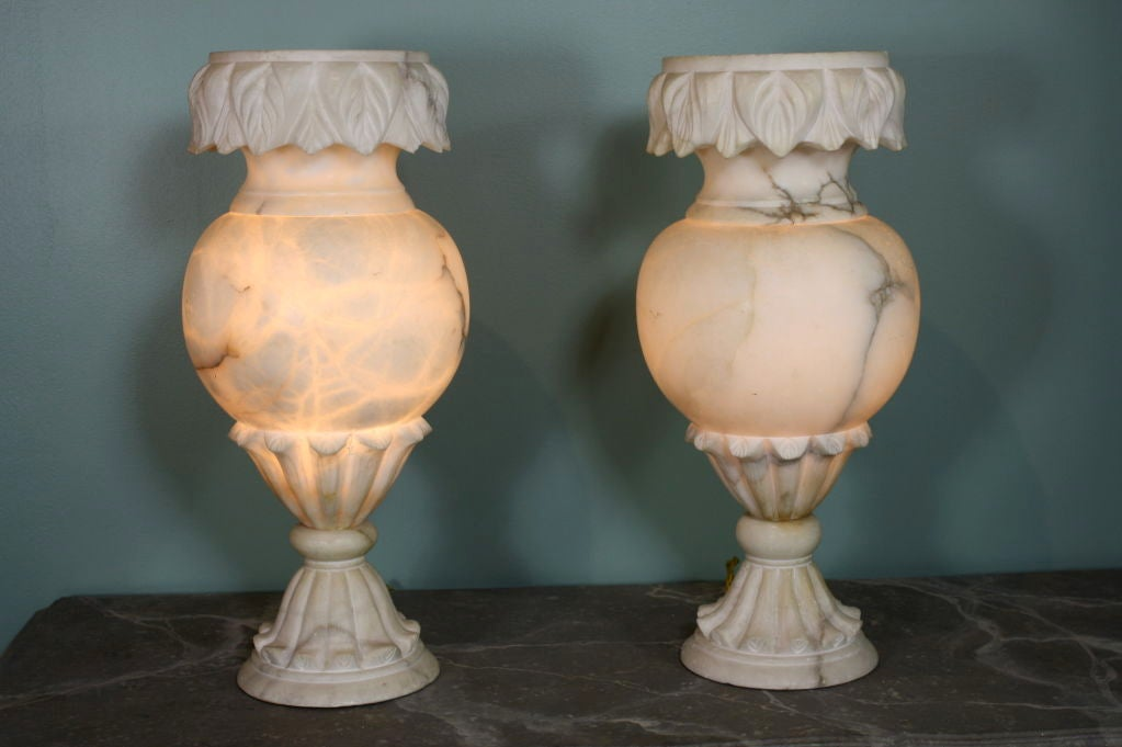 Pair of large, French carved alabaster vase-form lamps. Beautifully carved neoclassical details accent these vases, electrified as lamps and when lit are stunning in their appearance. The top part separates from the base.
