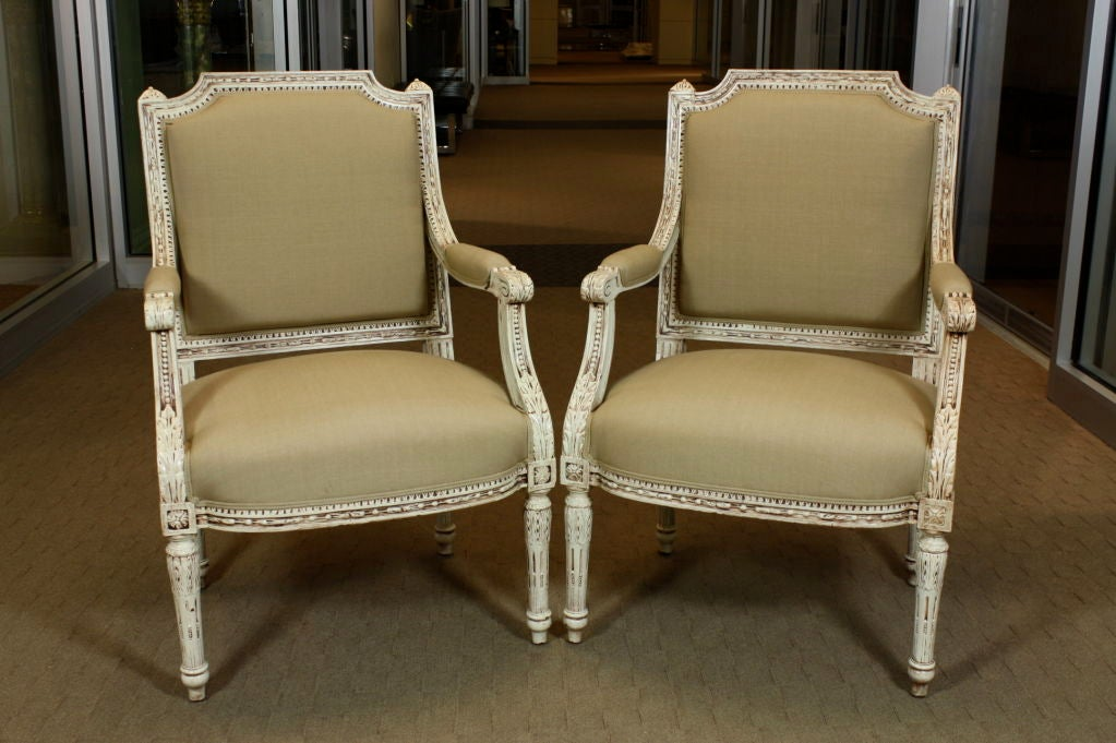 Pair of French white-painted Louis XVI style fauteuils with elaborately carved frames. Carved details include acanthus leaves, fluted legs, rosettes, water leaves and other neoclassical ornamentation. Newly upholstered in linen fabric.