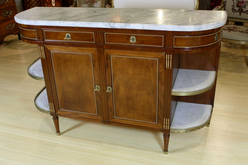 Elegant French mahogany buffet in the neoclassical style (circa 1920), with gilt-bronze mounts, detailed brass galleries, thick, nicely-veined white and grey marble top and marble top side shelves, working locks and keys. There are two drawers and