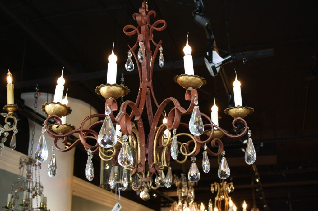 A unique French red polychromed iron chandelier in the Chinoiserie style with gilt-tole bobeches and gilded highlights, electrified with eight lights, and nice, large cut full-pear crystal drops (early 20th century, newly electrified). Price include