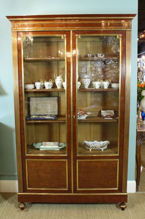 French Louis XVI style mahogany bookcase (or bibliotheque) with brass trim. The door panels are inset with contrasting