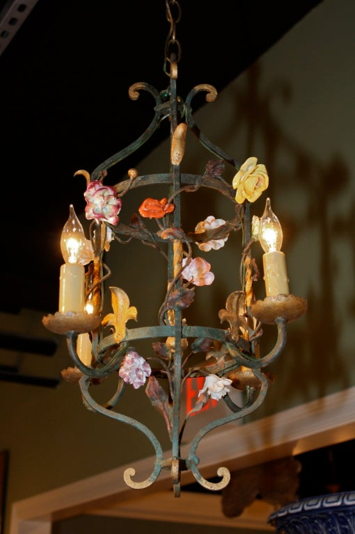 Petite French painted iron and tole leaf lantern, electrified with four lights. The lantern is embellished with twisting vines and colored Paris porcelain flowers, and gilded fleurs de lis. Price includes all rewiring, chain, ceiling canopy and bees