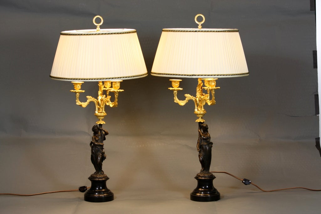 Pair of elegant gilded bronze and patinated bronze candelabra in the form of caryatids on black marble plinths, which have been converted into lamps with custom silk pleated shades.
