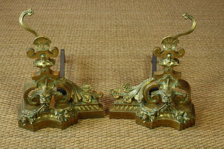 A pair of highly decorative French gilt-bronze andirons or chenets, with attached iron bars (circa 1870), in the form of fanciful dragons, with foliate berry, acanthus leaves and other naturalistic ornamentation typical of the Baroque style.
