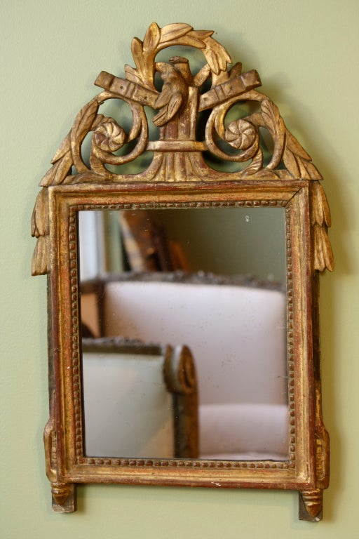 A petit French Louis XVI period giltwood mirror with a pair of doves and wreath cartouche, laurel leaves and other neoclassical detailing, and nice old mercury glass (