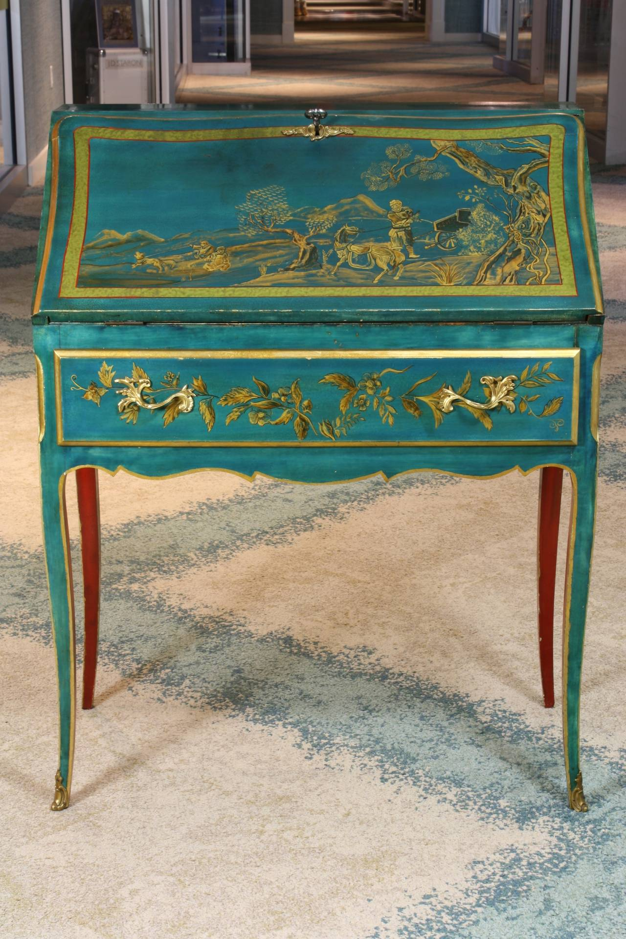 "A stunning, petite French slant-top desk or ""bureau de pente"" in the Louis XV style, turquoise and gold polychromed with Chinoiserie detailing, and red under-body.  Desk opens to reveal multiple smaller drawers, and has one larger drawer underneath."