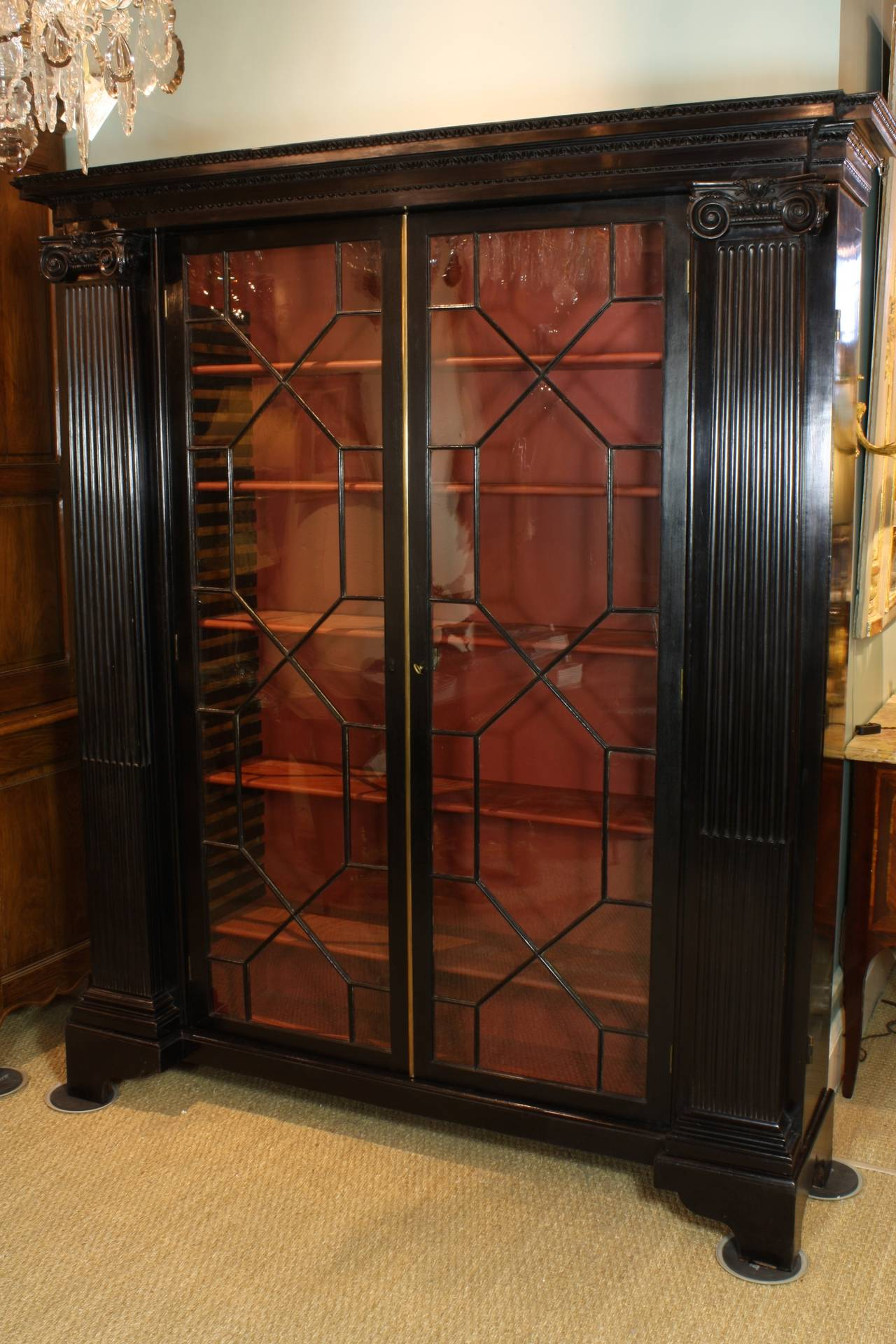A rare English black-lacquered bookcase or credenza with astragal glazed front doors (late 19th century). Ionic pilasters with cabled fluting flank each side, and open to display secret inner shelves (the pilaster-ornamented doors also lock). Five