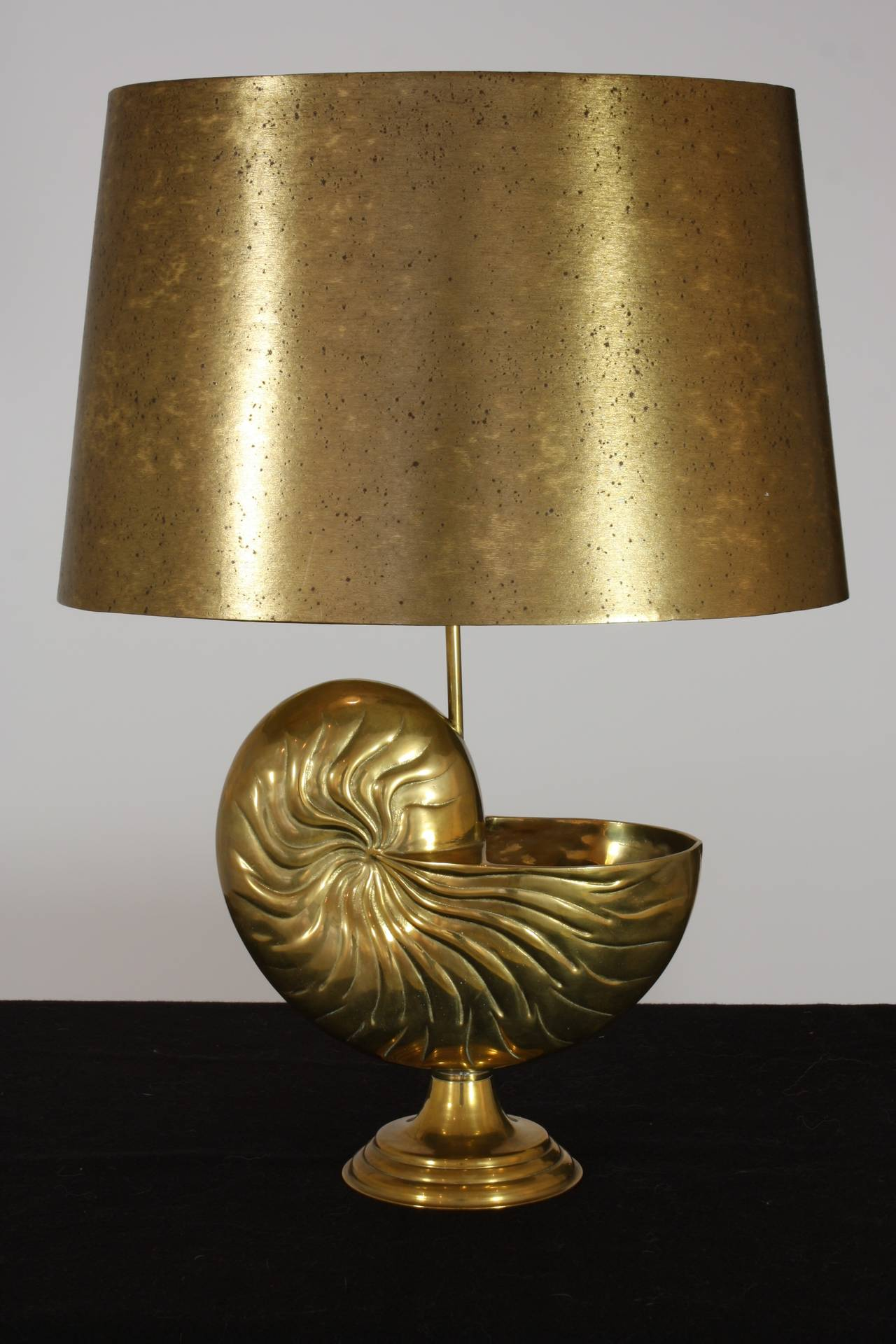 An unusual French bronze nautilus form table lamp with faux-brass paper shade (in the style of Maison Charles), mid-20th century. The lamp has been re-electrified for U.S.