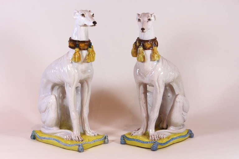 A pair of large Italian glazed ceramic grey-hounds with lovely buckled and tasseled collars, representing a male and female, seated on tasseled cushions.