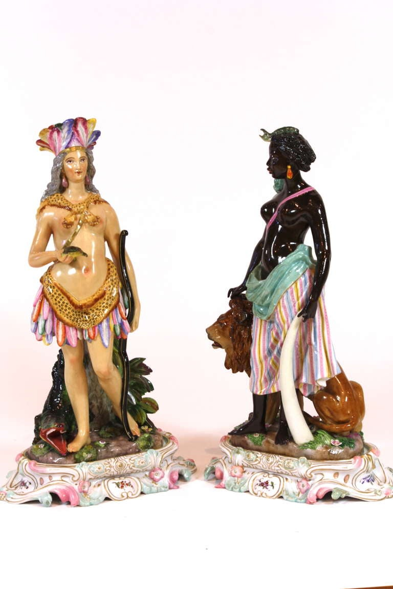An unusually large, and very decorative pair of beautifully-painted Meissen porcelain figures representing the two continents:  America, with her highly-stylized native Indian dress, bow and arrow and alligator; and Africa, holding an elephant tusk,