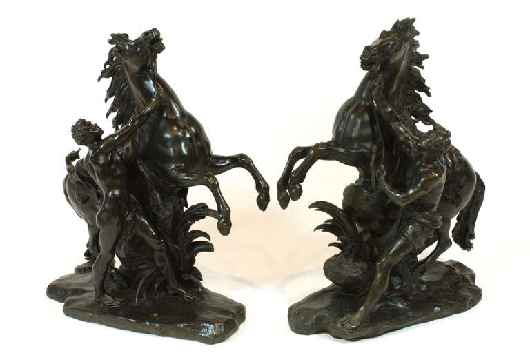 Pair of 19th century French patinated bronze sculptures of the Marly horses. These two sculptures were modeled after the large marble sculptures representing wild horses restrained by grooms, commissioned in 1739 by King Louis XV from the sculptor,