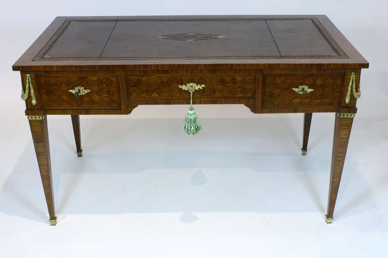 A high-quality French Louis XVI style desk with geometric parquetry in mahogany with gilt-bronze mounts, including swags at the corners. The desk has three drawers with working locks and keys and is double faced. The right drawer features a