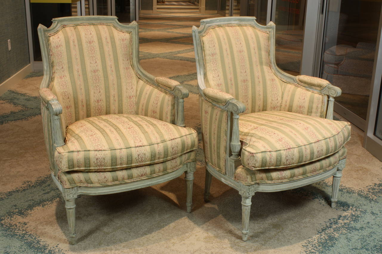 Pair of French Louis XVI style painted bergeres with separate seat cushions. The bergeres feature