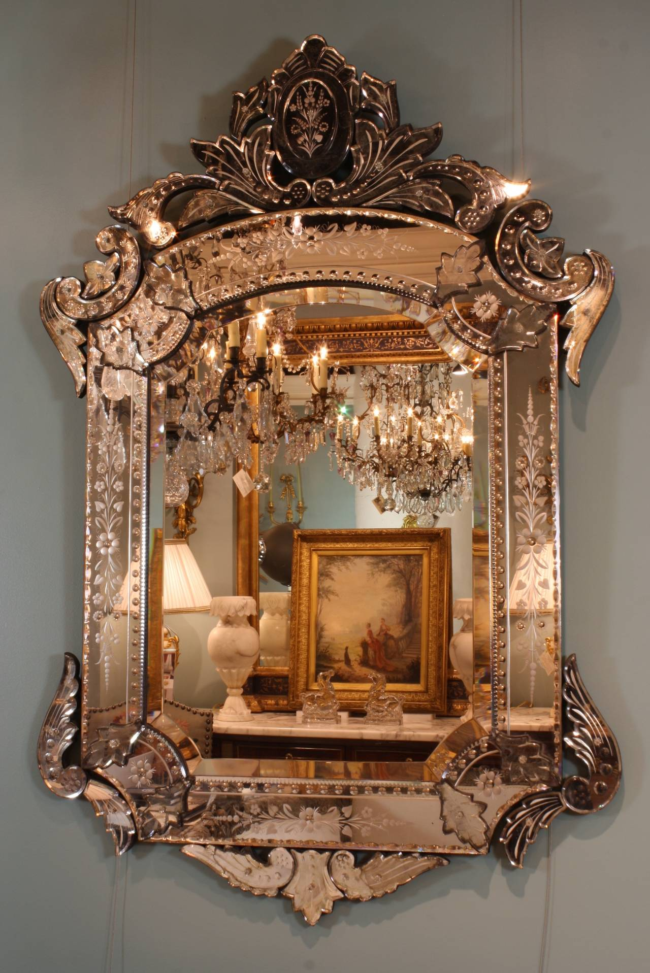 "A beautifully-detailed Venetian mirror in the Rococo style with bevelled glass, detailed cartouche, ""C"" scrolls, acanthus leaves, etched floral designs and bubble designs."