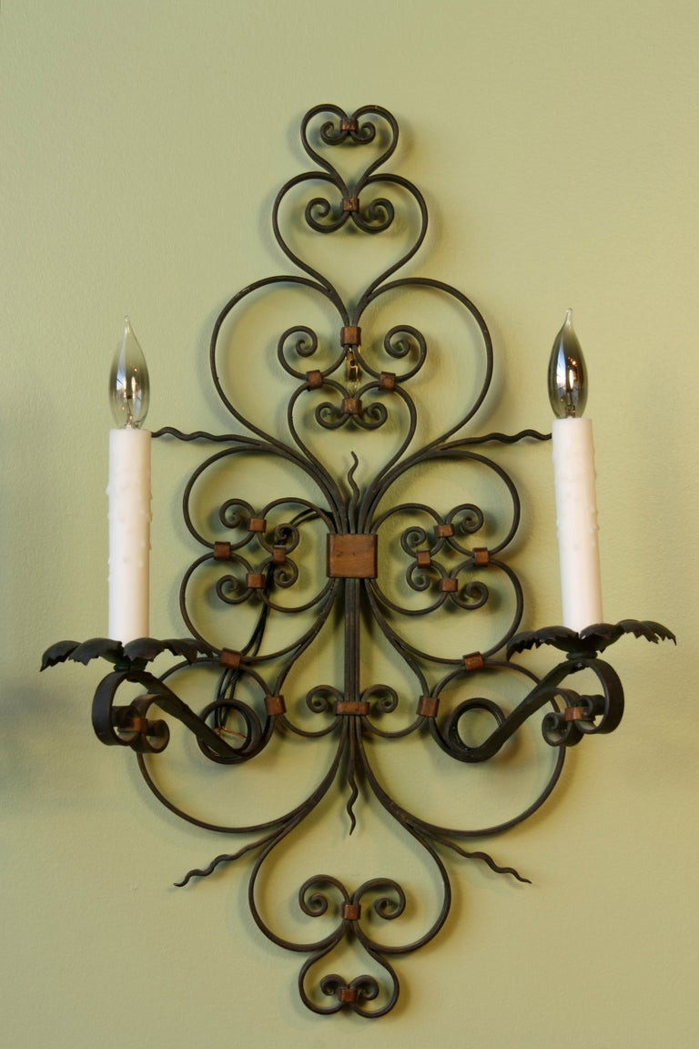 Pair of large French provincial wrought iron two-arm sconces with parcel-gilt and dark green paint. These sconces have been newly-rewired and have beeswax candle sleeves, and would make a charming addition to a French country or rustic interior.