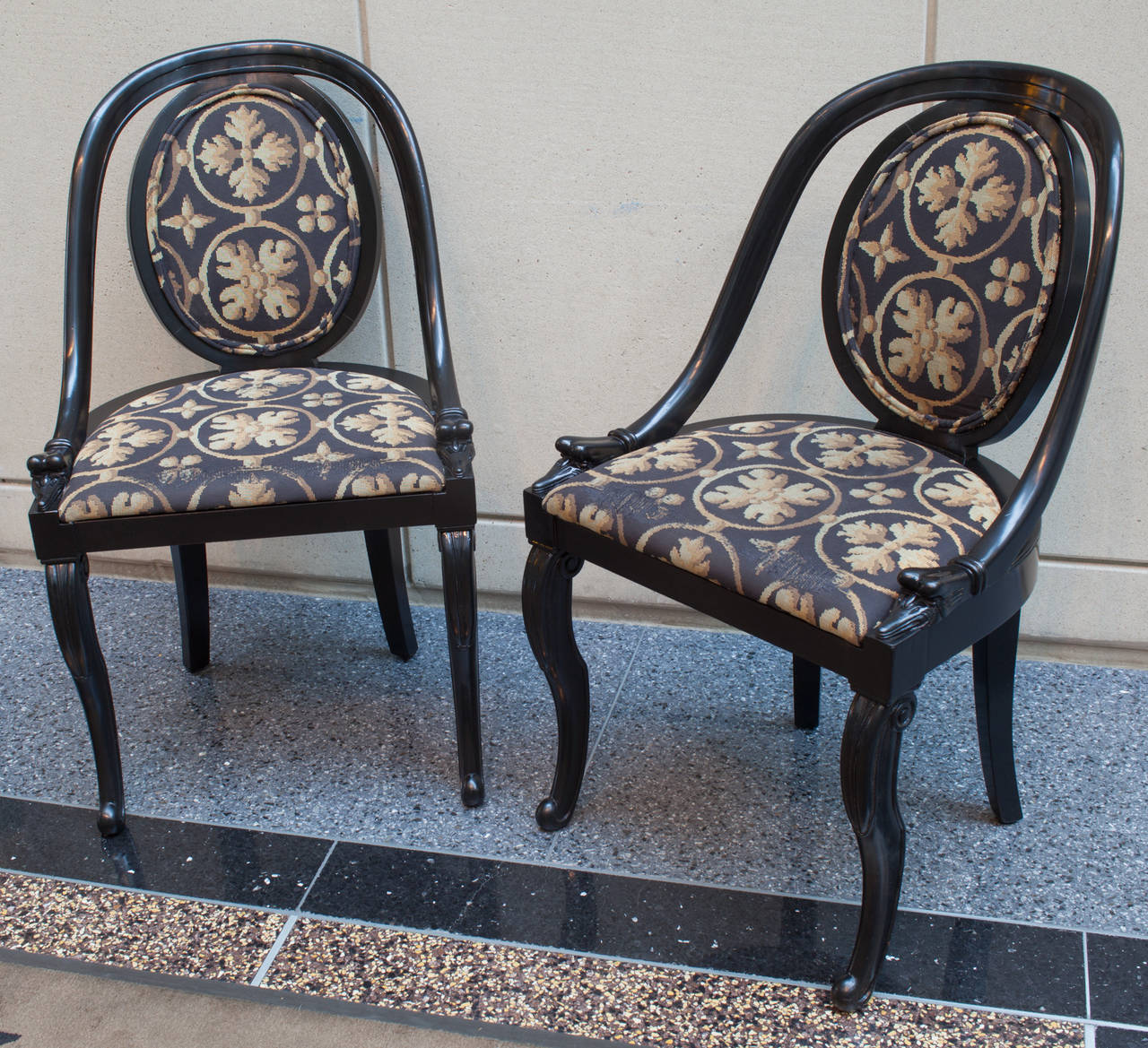 This pair of black lacquer spoon back chairs have a very graceful form. The oval backrest, the sloping arms and the very graceful cabriole front legs terminating in a scroll foot. The tapestry is worn at the seat front.