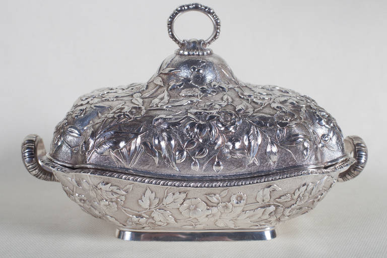 Sterling silver covered  serving dish in a floral repoussé pattern by Theodore B. Starr. The weight is approximately 45 troy ounces. The ring handle on the cover is fixed. There is a handle on each side and the bottom half has a gadrooned