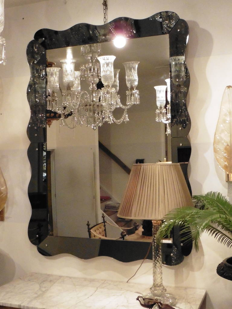An elegant and large Venetian style mirror with a scalloped grey mirrored frame, France, circa 1960.
