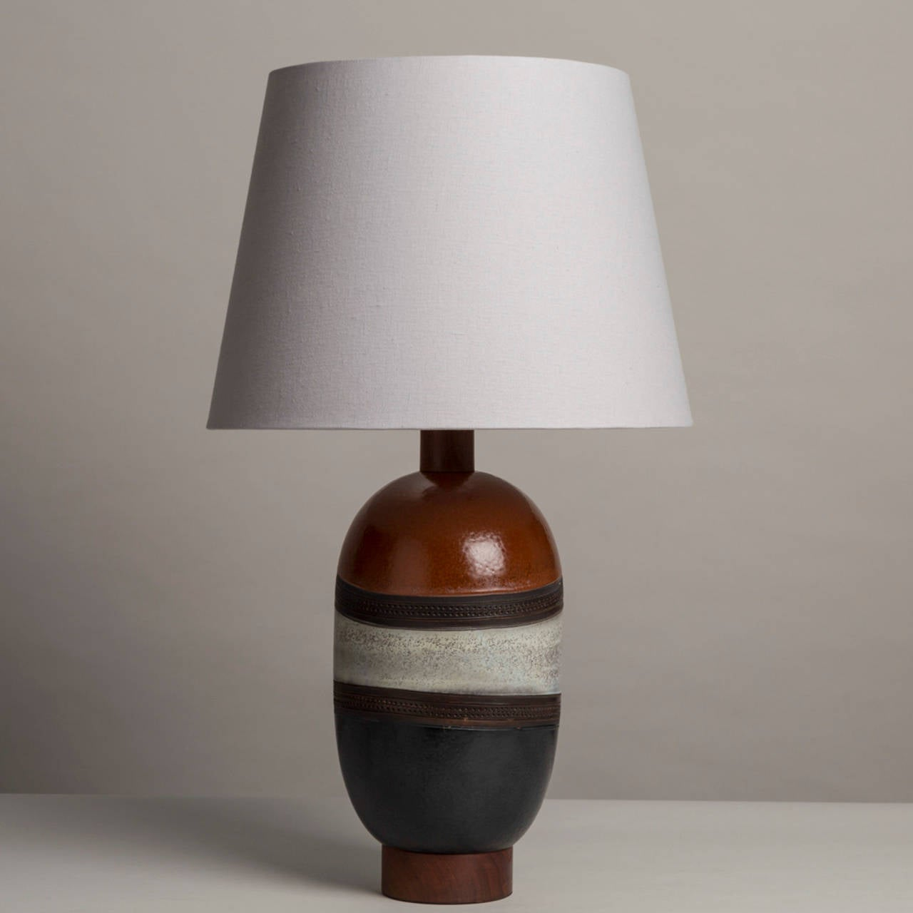 Single Italian glazed ceramic table lamp with brown, off white and black sectioned off with deep brown stimpled banding.  The lamp is set on a wooden base and has been furnished with an off white linen shade. 1970s.