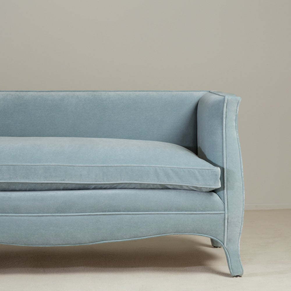A standard high back French style powder blue velvet upholstered sofa by Talisman Bespoke.   Unusual and elegant, this signature Talisman Bespoke sofa is inspired by a unique French, 20th century design. This sofa is available in a variety of