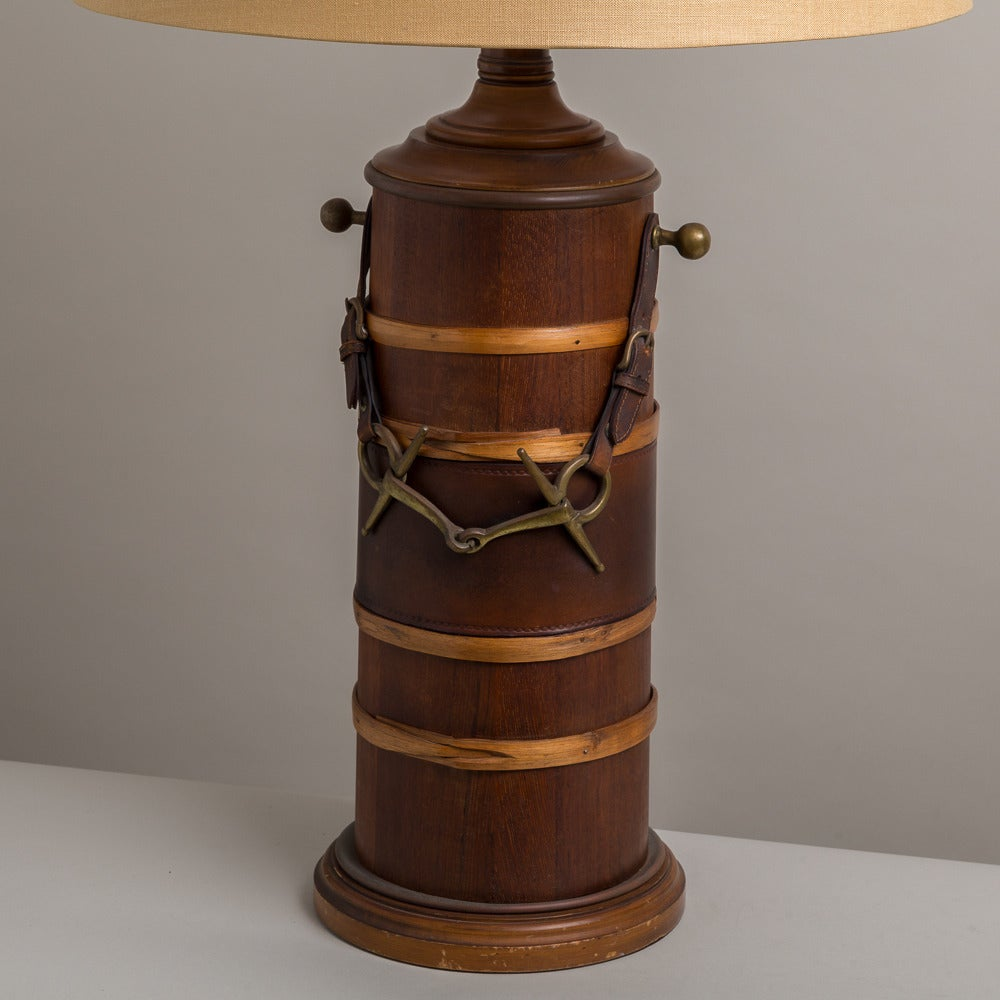A single wooden lamp with lighter wood bands and brass and leather 'riding bit' decoration designed by Paul Hansen coupled with a linen shade. 1950s  Prices include 20% VAT which is removed for items shipped outside the EU.
