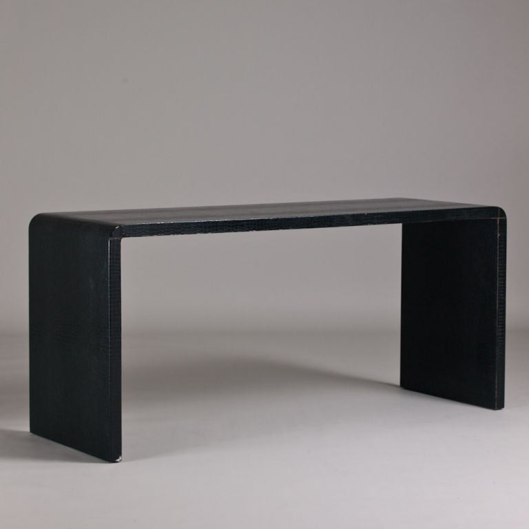 a black faux leather wrapped waterfall shaped console