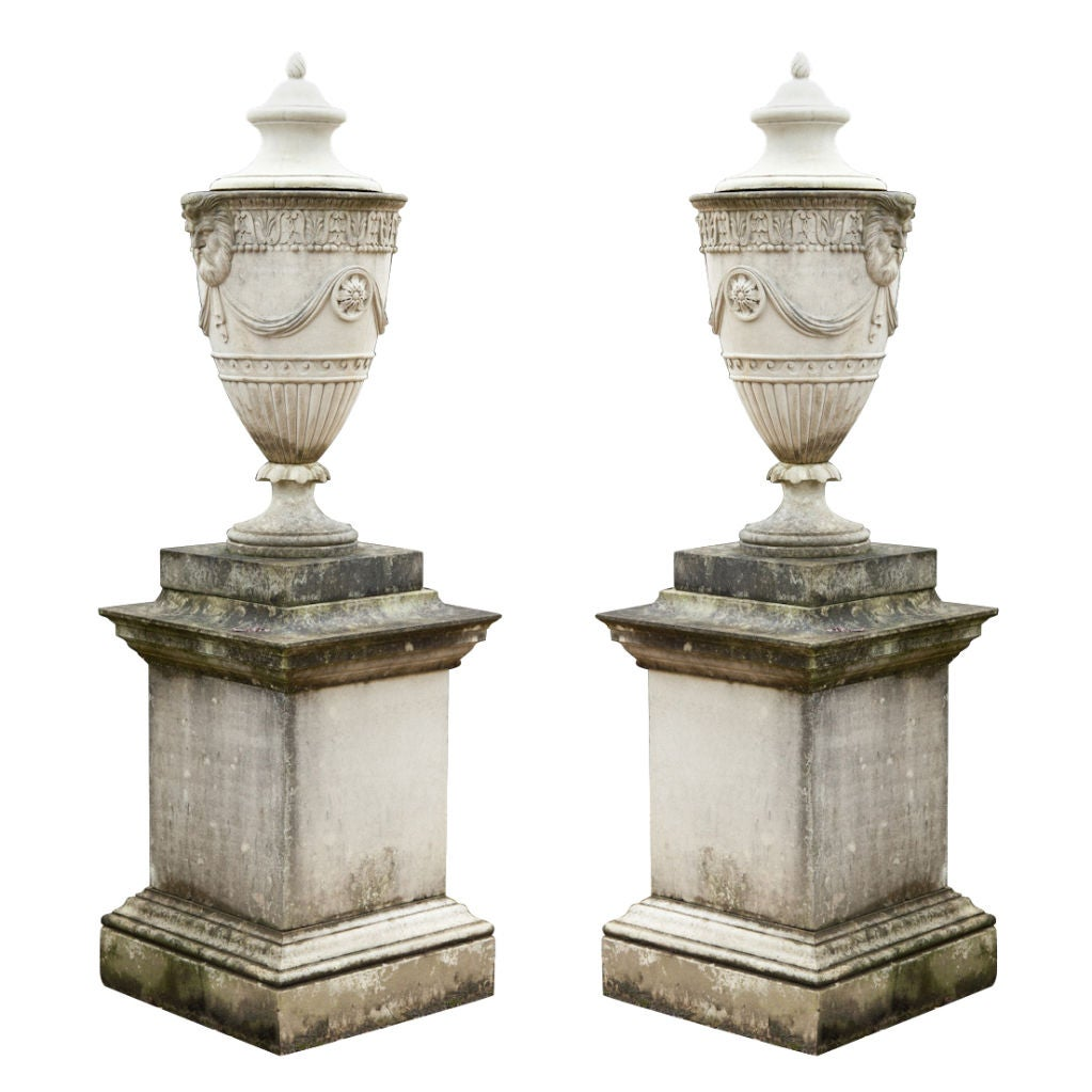 a pair of adam style composition stone lidded urns on