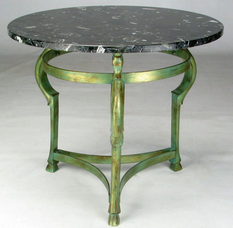 Cast bronze side table under a green and gilt patina. The three legs feature sea horse heads, each based in a hoofed foot, and joined by a trefoil stretcher. The marble top is a lovely black with white veining. Most likely of Italian origin.