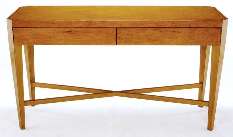 Art moderne style console table by designer Nancy Corzine. The clean lines incorporate canted legs that are supported by a large X-base stretcher. Two flush drawers with a scored border top provide storage. Constructed of a beautiful aged and glazed