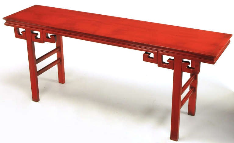 Carved and lacquered Chinoiserie altar table or console in the style of James Mont. Squared dowel legs with double side stretchers and triple Greek key brackets. Finished on both sides and lacquered in an aged cinnabar, with black glaze overlay.
