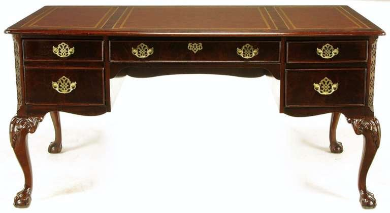 Sligh of Holland, Michigan Regency style desk in rich mahogany with flame drawer fronts and burled border around the three piece tooled red leather top. Cabriole legs with carved top detailing and ball and claw feet. Brass pierced escutcheons with