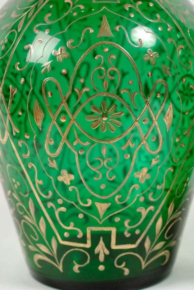 Tall and impressive, these huge green decanters have blown glass bodies with allover gold leaf foliate decoration. Equally impressive are the stunning stoppers, which are blown glass that was then cut into a form resembling obelisks. Believed to be