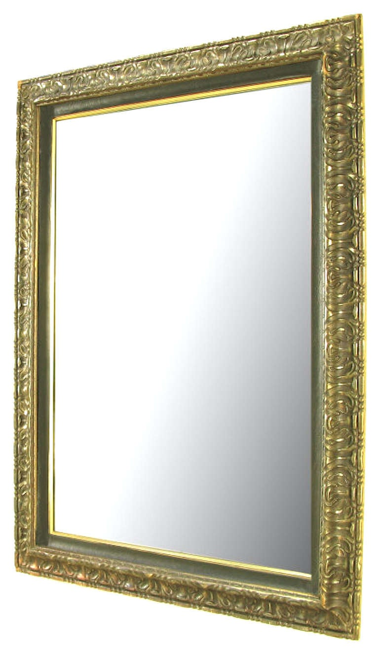 Hand carved and gilt wall mirror with leather like inner border and brass beading.