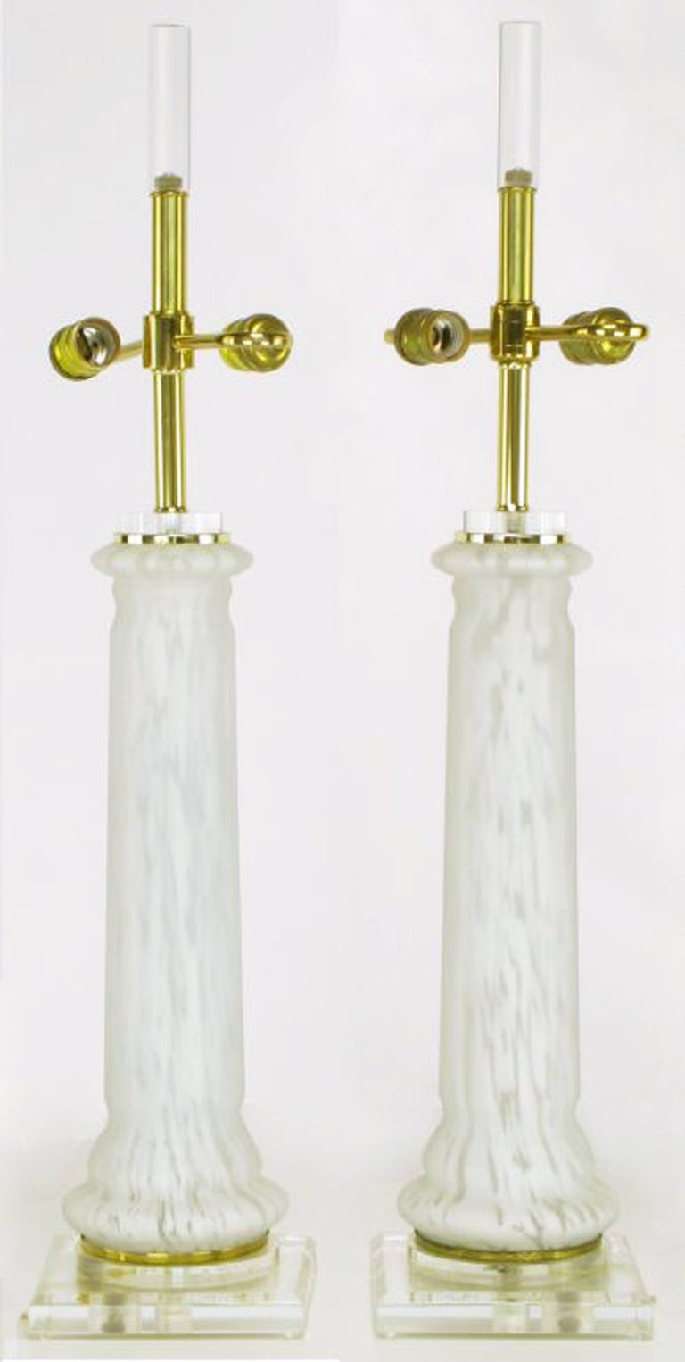 Beautiful hand blown white and clear Murano glass column form table lamps from Bauer Lamp. The base is a Lucite and brass plinth, echoing the brass and Lucite capital. Double socket illumination, and finished in tall rectangular Lucite finial.