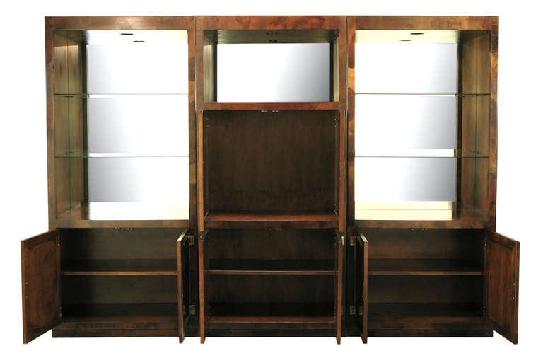 Exceptional three-piece oyster burl Campaign wall unit by Hekman Furniture. Two outer cabinets feature open glass shelving with mirrored backs and a two door lower cabinet with single shelf. The centre unit features a pair of two-door cabinet