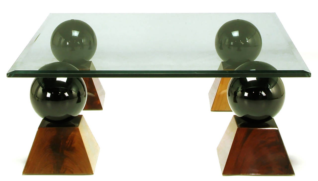 Four black gloss lacquered resin balls surmount burled mahogany truncated pyramids, supporting a square 5/8