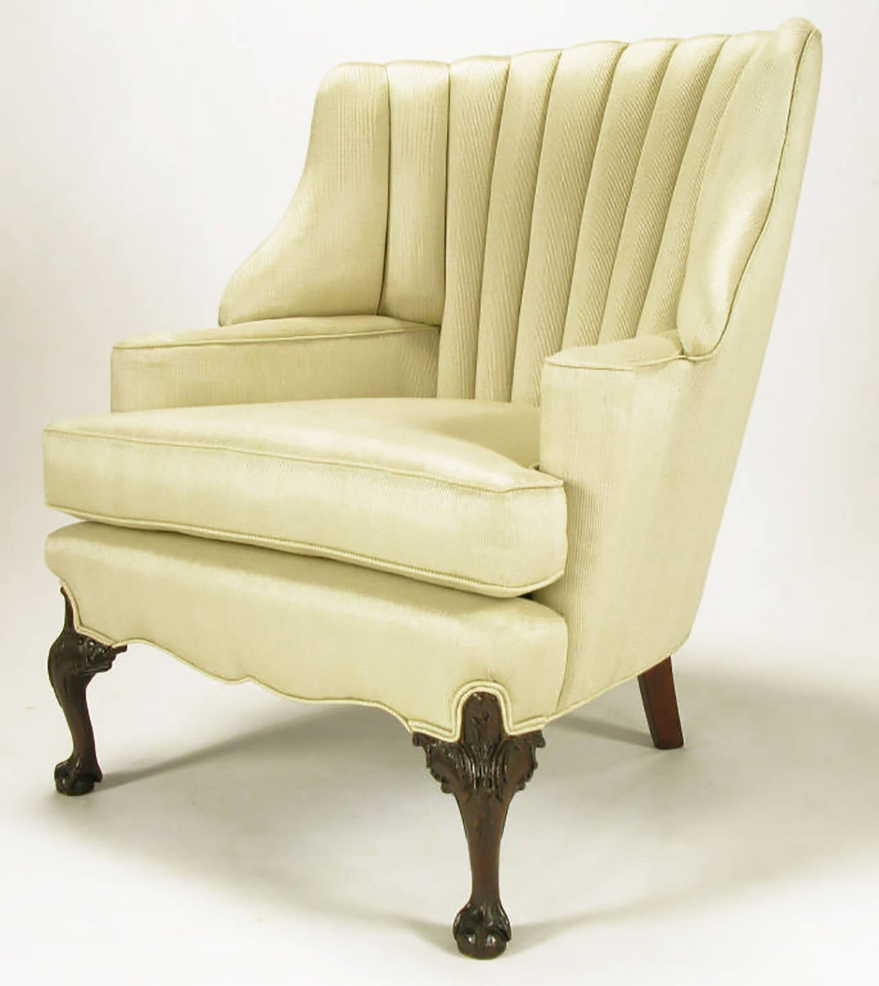 Restored barrel and channeled back Regency wide wing chair. New silk upholstery with tactile all vertical pin striping. Rolled end arms with sinuous front apron and heavily carved mahogany ball and claw front legs. Uncommon front roll to the deepset