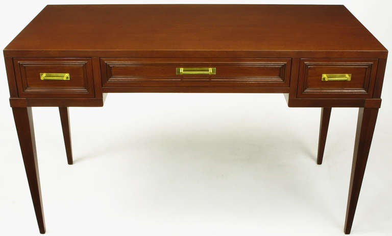 Elegant and modern mahogany three drawer writing table from Fine Arts Furniture, Grand Rapids MI, a venerable name in Grand Rapids furniture history. Twisted Brass bar pulls with simple rectangular escutcheon, framed drawers, and tapered legs.
