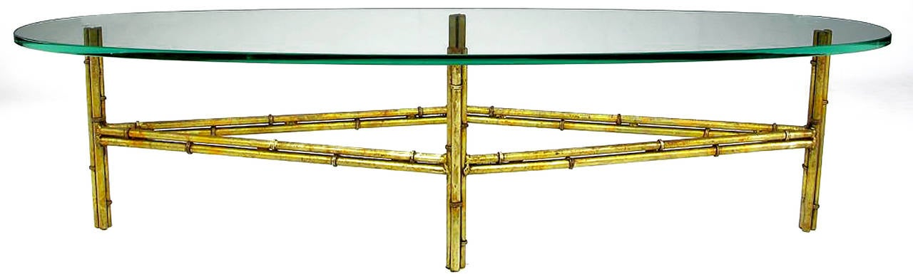 Excellent design and patina, this gilt metal bamboo form coffee table features a unique diamond-shaped base. The gold leaf finish has a beautiful patina with some of the red bole showing through. Measure: The glass surf board (elliptical) top is
