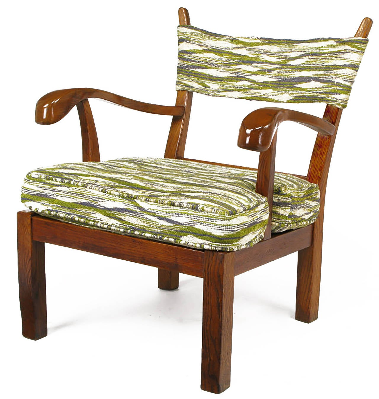 Oak lounge chair upholstered in green, violet blue, and cream fabric, handwoven in the manner of Dorothy Liebes. One-piece strap back supported by tapered risers with carved and exaggerated arms. Chunky squared legs and seat frame.