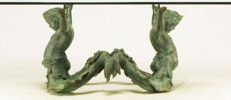 Elegant and unusual dining table of patinated bronze and glass. The bronze base depicts a pair of aquatic cherubs, or mermen, with outstretched arms supporting a 3/4