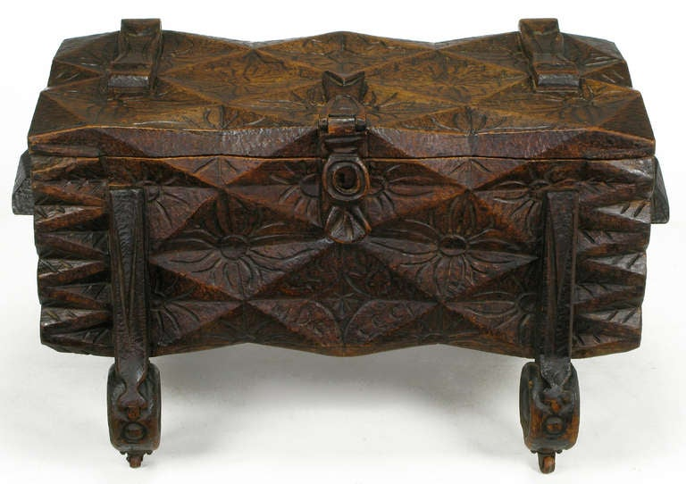 Heavily carved Spanish Gothic-style wooden trunk with diamond pattern inverted rosettes. Carved wood latch, front legs and decorative carved hinge straps to the top. Easily mobile with original wood wheel casters.