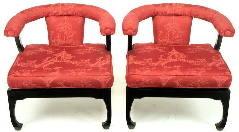 Pair of chinoiserie lounge chairs with black lacquered Ming style legs and apron. Red pagoda scene printed silk upholstered seat, back and curved arms. Uncommon, and likely custom, variation of the more common low yoke backed lounge chairs offered