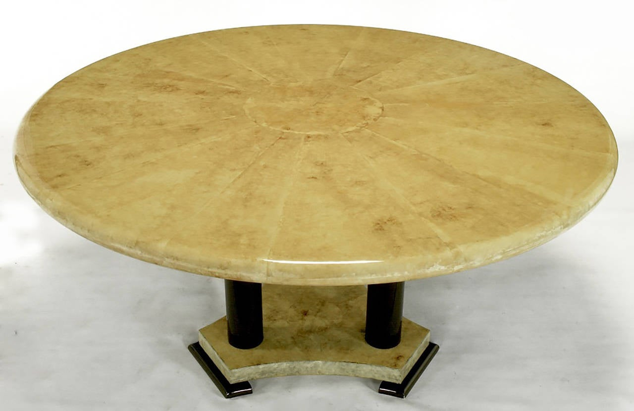 A stunning Empire style dining table, with a heavily lacquered goatskin top in a sunburst pattern. The top is supported by three dark chocolate brown lacquer columns and feet, with lacquered goatskin covering the intervening trihedral base.