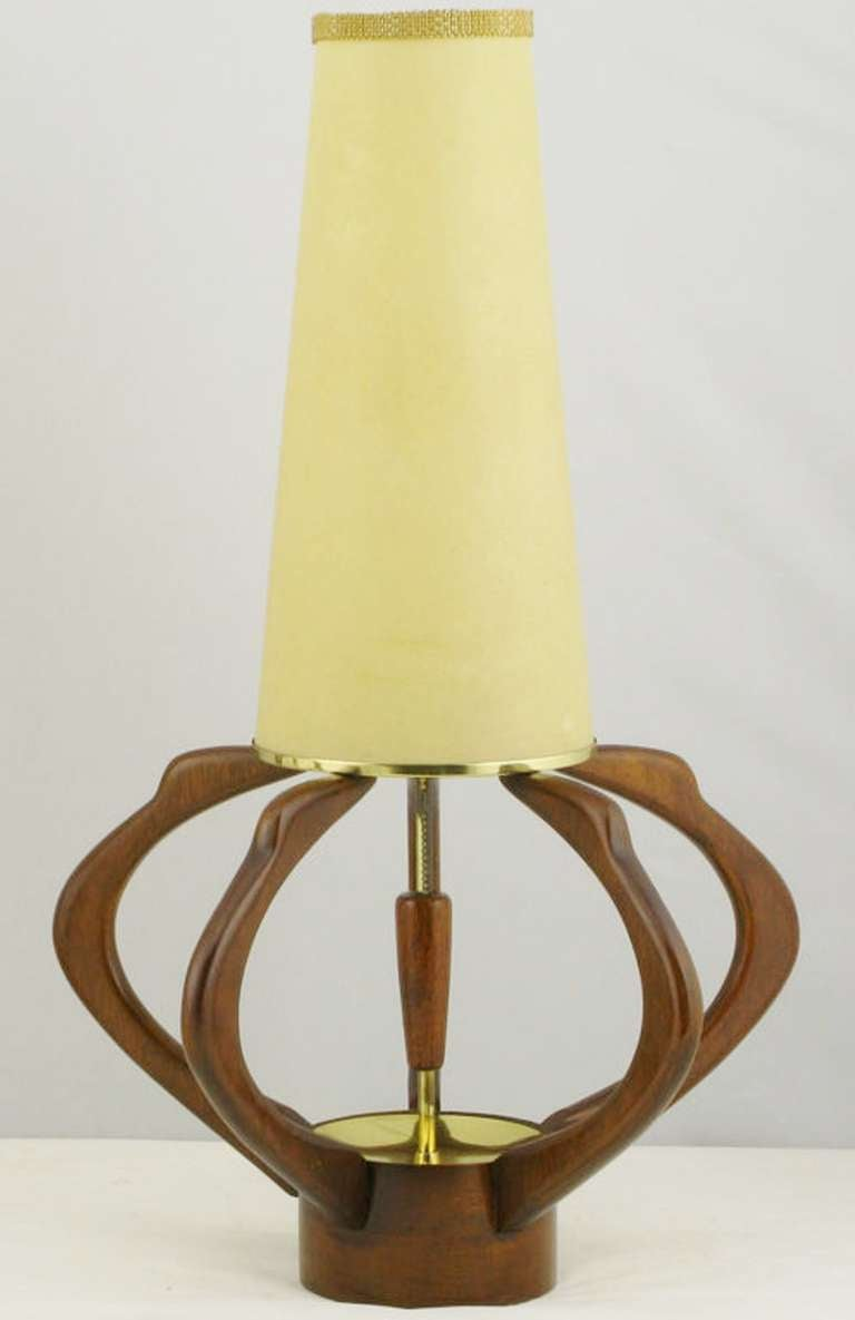 A unique pair of teak and brass table lamps. The slender conical textured paper shades are attached to the brass and teak center post. Melon-shaped ribs with a solid teak base.