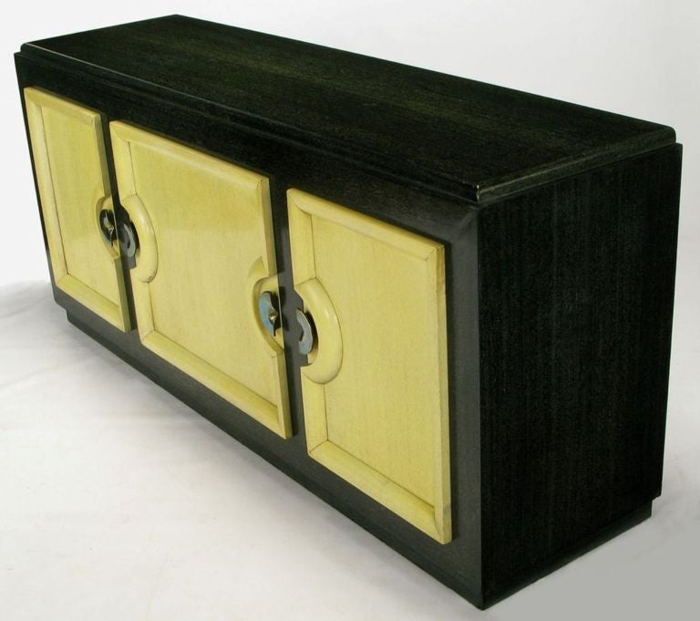 Black and ivory cerused lacquer finish and aged brass demilune pulls on this sleek sideboard by Stewartstown Furniture Company. The maker was a Pennsylvania furniture manufacturer located in Stewartstown, near the furniture making center around Red
