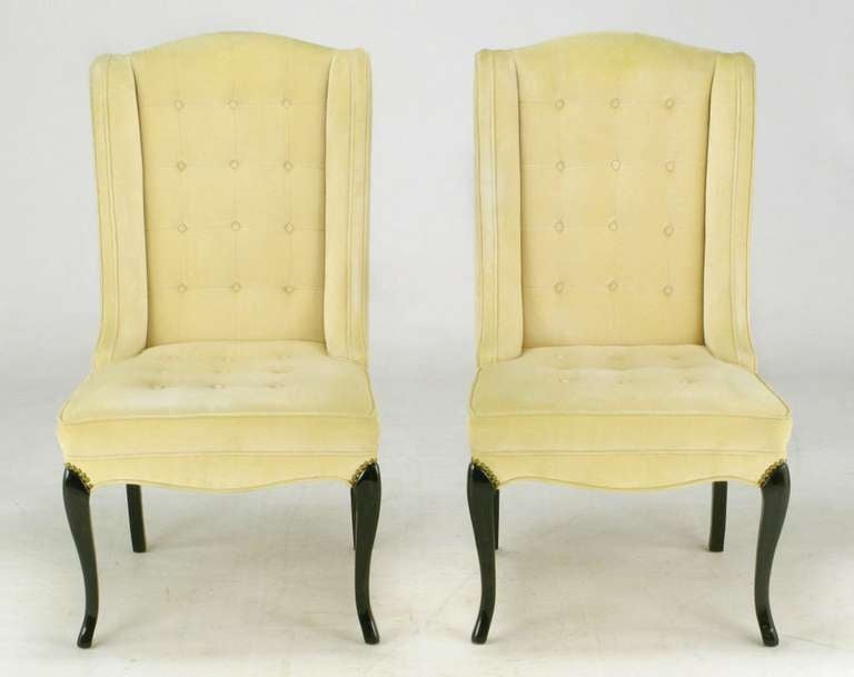 Elegant pair of creamy camel velvet clad slipper chairs, with button tufted seats and backs. Sinuous front and back carved wood legs are detailed with brass nailhead trim.