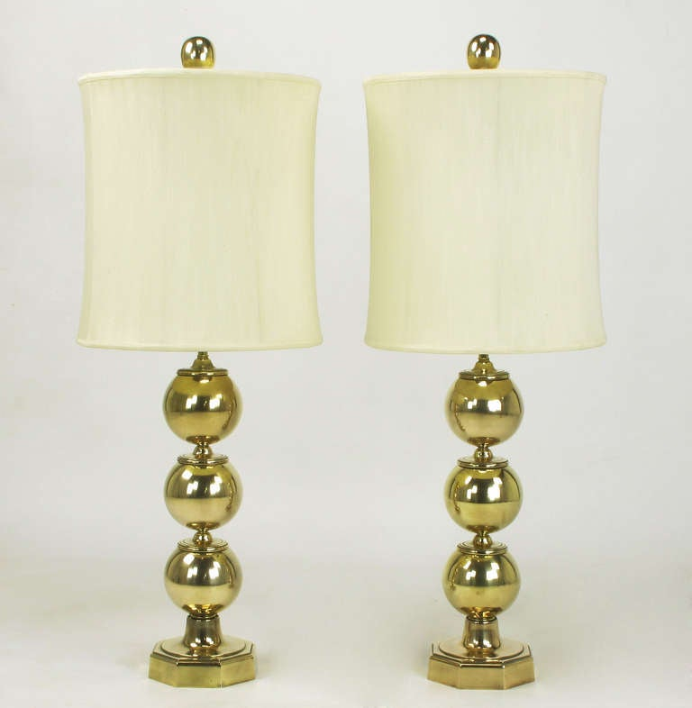 Elegant pair of cast brass stacked ball table lamps. Cast from 100% brass, each ball has a ringed saucer cap. Octagonal base with a round flange. Brass stem and double socket cluster with an egg shaped brass ball finial. Sold sans shades.