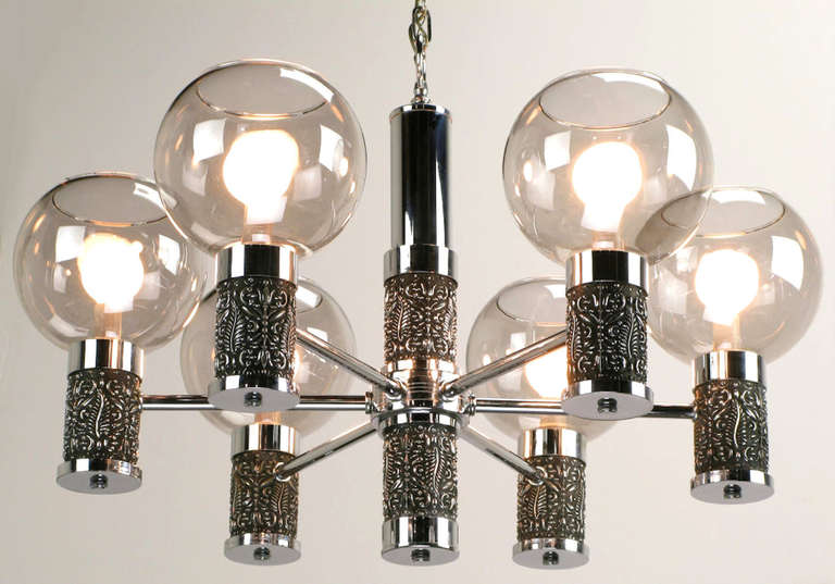 Six-arm chandelier combines chrome-plated metal and cast chrome-plated relief. Cylinders at the center and on each arm are cast resin with an antiqued chrome finish.